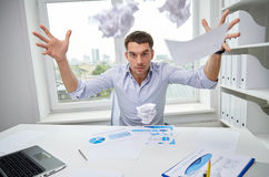 Angry businessman throwing papers in office Royalty Free Stock Photo