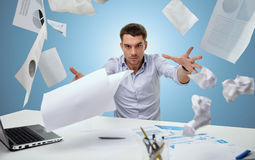 Angry businessman throwing papers in office Royalty Free Stock Image