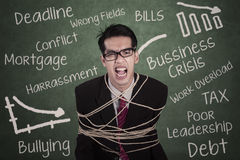 Angry businessman tied with rope in class Royalty Free Stock Images
