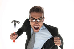 Angry businessman about to hammer on white background. Closeup of angry and fierce looking mature guy with hammer stock photo
