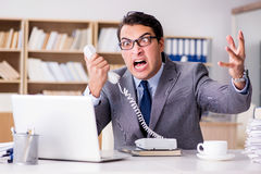 The angry businessman with too much work in office Stock Images