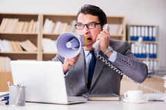 The angry businessman with too much work in office stock photography