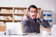 The angry businessman with too much work in office Royalty Free Stock Images