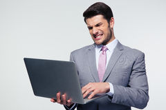Angry businessman using laptop Stock Images