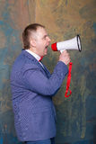 Angry businessman using megaphone over grey background Stock Image