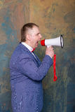 Angry businessman using megaphone over grey background Stock Photo