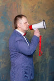 Angry businessman using megaphone over grey background.  Royalty Free Stock Photos