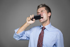 Angry businessman. Very angry businessman si biting his mobile phone Stock Photo