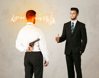 Angry businessman with weapon. Angry businessman hiding a weapon behind his back Royalty Free Stock Photos