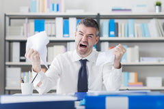 Angry businessman working at office desk Royalty Free Stock Images