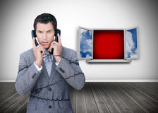 Angry businessman wrapped in cables phoning Royalty Free Stock Image