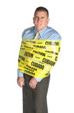 Angry businessman wrapped in caution tape. An angry businessman wrapped in caution tape as a warning to coworkers snarls as a result of stress and frustration Stock Image