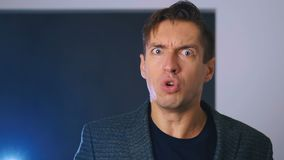 Angry businessman yelling at camera closeup. Aggressive man yells at the interlocutor, threatening with his finger. The