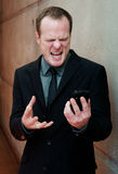 Angry businessman, yelling at cell phone. Standing inside a building Royalty Free Stock Image