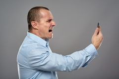 Angry businessman yelling at cellphone Royalty Free Stock Images
