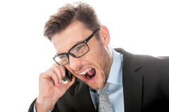 Angry businessman yelling into cellphone on white. Royalty Free Stock Photos