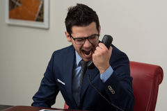 Angry Businessman Yelling Into A Cellphone. Young Businessman Working At His Computer While Talking On The Phone Stock Photo