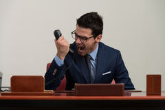 Angry Businessman Yelling Into A Cellphone. Young Businessman Working At His Computer While Talking On The Phone Stock Photography