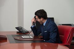 Angry Businessman Yelling Into A Cellphone. Young Businessman Working At His Computer While Talking On The Phone Royalty Free Stock Images