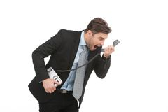 Angry businessman yelling into landline phone on white. Royalty Free Stock Photos