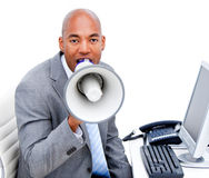 Angry businessman yelling through a megaphone Royalty Free Stock Photography