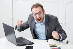 Angry businessman yelling. Nervous professional at the desk, yelling because something went wrong Stock Photography