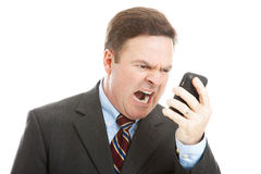 Angry Businessman Yelling into Phone. Angry businessman yelling into a cellphone.  Isolated on white Stock Photo