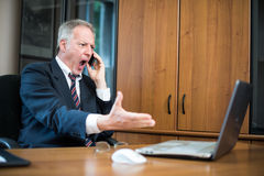 Angry businessman yelling at phone Royalty Free Stock Image