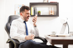 Angry businessman yelling at the phone. Profile view of a furious businessman yelling to a phone while seating in front of his desk in an office Stock Photo