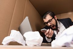 Businessman yelling at smartphone. Angry businessman yelling at smartphone in box Stock Images