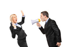 Angry businessman yelling via megaphone to a woman. Angry businessman yelling via megaphone to a businesswoman isolated on white background Stock Images