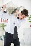 Angry Businessman. Youn angry Businessman standing in the office and holding a laptop as if to wants break it Stock Photo