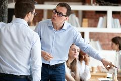 Angry businessmen colleagues quarrelling in shared office stock images