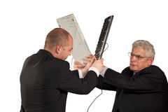 Angry businessmen fighting with keyboards Stock Image