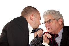 Angry businessmen tearing at their ties. Two angry businessmen standing face to face and tearing each others tie Royalty Free Stock Image
