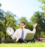 Angry businessperson with laptop sitting on grass and looking at. Young angry businessperson with laptop sitting on green grass and looking at clock in a park Stock Images