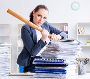 Angry businesswoman with baseball bat in office