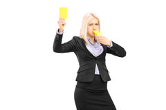Angry businesswoman blowing a whistle and showing a yellow card. Isolated on white background Stock Photos