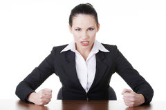 Angry businesswoman at the desk Stock Image