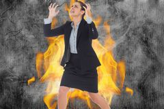 Angry businesswoman gesturing against fire. Digital composite of Angry businesswoman gesturing against fire Stock Images