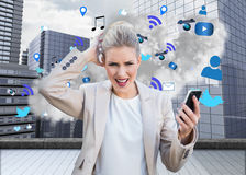 Angry businesswoman holding smartphone with cloud computing graphic Stock Photos