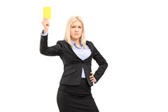 Angry businesswoman holding a yellow card. Isolated on white background Stock Image