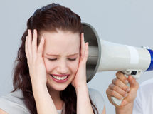 Angry businesswoman listening to a megaphone Stock Photography