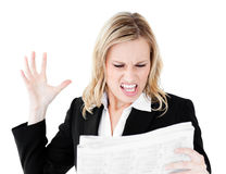 Angry businesswoman looking at newspaper shouting Royalty Free Stock Images