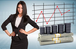 Angry businesswoman with packs dollars and barrels Royalty Free Stock Image