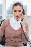 Angry businesswoman picking up the phone Stock Image
