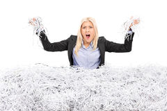 Angry businesswoman in a pile of shredded paper Royalty Free Stock Photos