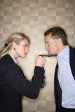 Angry Businesswoman Pulling Man's Tie. Caucasian mid-adult businesswoman staring into eyes of a middle-aged businessman while pulling angrily on his tie Royalty Free Stock Images