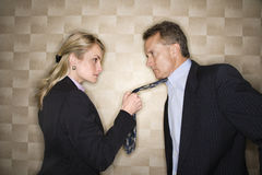 Angry Businesswoman Pulling Man's Tie Royalty Free Stock Photography