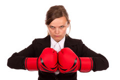 Angry businesswoman punching red boxing gloves together ready to Stock Photo